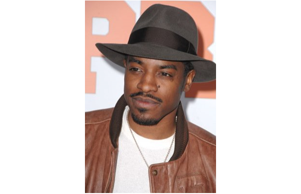 Andre 3000 in varsity leather, a white tee, and a  hat
