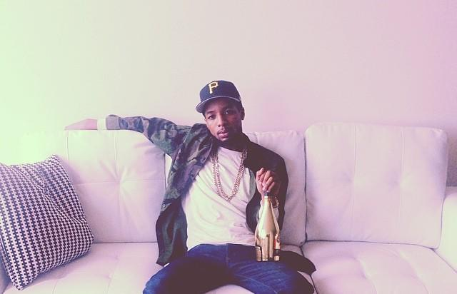 Rockie Fresh on a couch with a bottle of Ace Of Spades