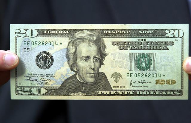The new design for the twenty dollar bill is held by a man October 9, 2003 in New York City. The new currency includes improved security features and subtle background colors of green, peach and blue to help prevent and detect counterfeiting.