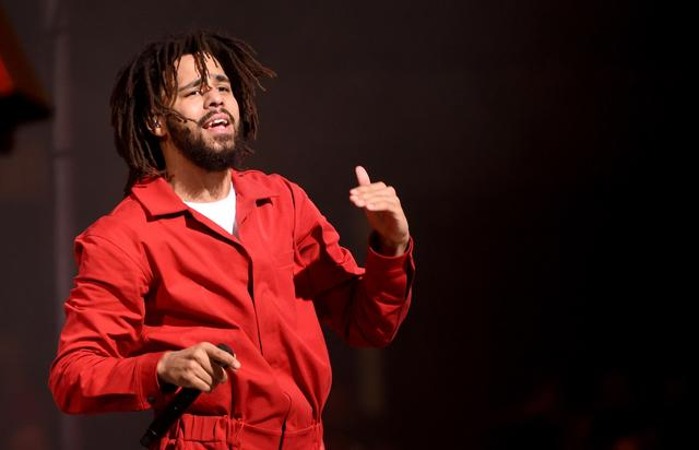 J. Cole performing in a red jumpsuit