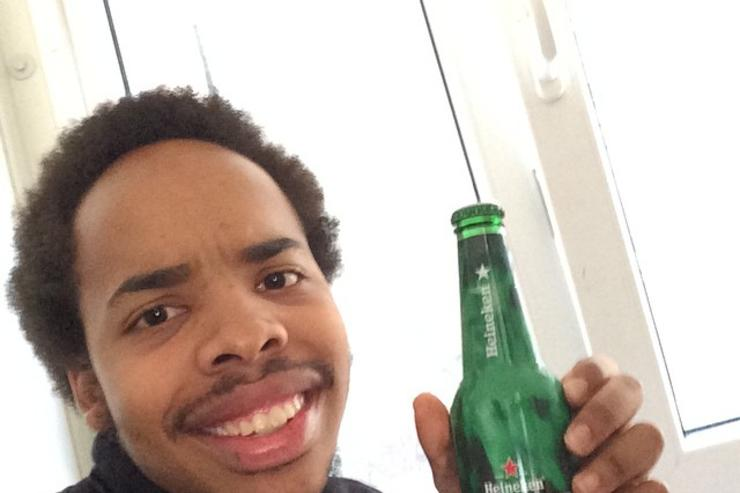 Earl Sweatshirt showing off glass bottle