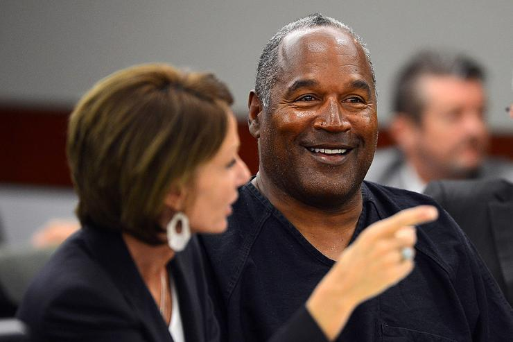 O.J. Simpson (R) smiles as he confers with his defense attorney Patricia Palm at the end of an evidentiary hearing in Clark County District Court on May 17, 2013 in Las Vegas, Nevada. Simpson, who is currently serving a nine-to-33-year sentence in state prison as a result of his October 2008 conviction for armed robbery and kidnapping charges, is using a writ of habeas corpus to seek a new trial, claiming he had such bad representation that his conviction should be reversed.